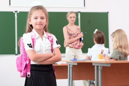 portrait of schoolgirl with a school backpack, in the background a classroom and the teacher tells the class photo