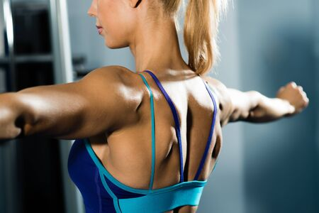 female athlete straining back muscles and arms, do sport in the fitness club Stock Photo - 17012372