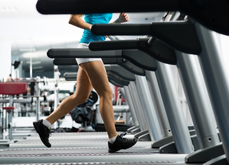 cardio workout: woman running on a treadmill in a fitness club, sport in the fitness club Stock Photo