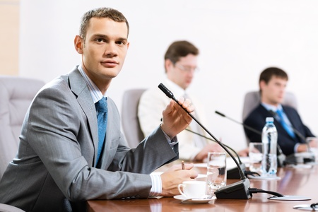 Portrait of a businessman, said into the microphone, in the background colleagues communicate with each other Stock Photo - 17047090