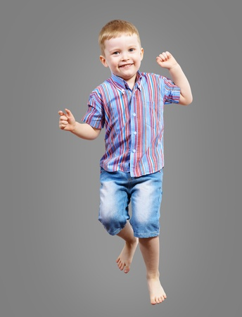 boy jumping hands up smiling and happy photo