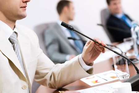 businessman, said into the microphone, in the background colleagues communicate with each other Stock Photo - 17047087