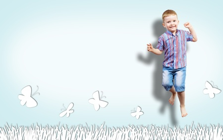 boy jumping on the background of painted wall with grass, clouds and butterfly collage of a happy childhood, place for text photo