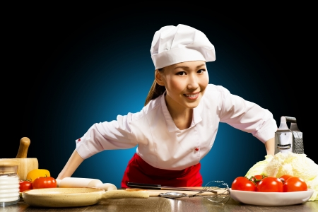 executive assistants: Asian woman cook leaned over the table and looking into the camera Stock Photo