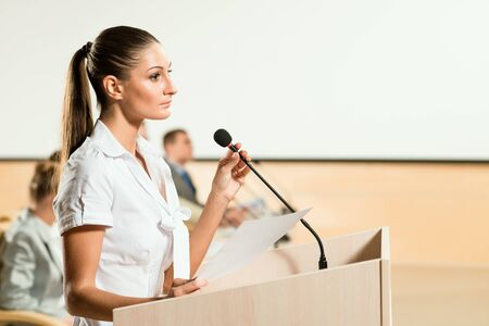 Portrait of a business woman holding a microphone and looks ahead Stock Photo - 17078936