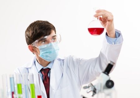 scientist working in the lab, in protective mask, examines a test tube with liquid Stock Photo - 17078919