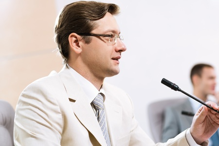 Portrait of a businessman, said into the microphone, in the background colleagues communicate with each other Stock Photo - 17079162