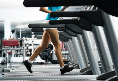woman running on a treadmill in a fitness club, sport in the fitness club photo