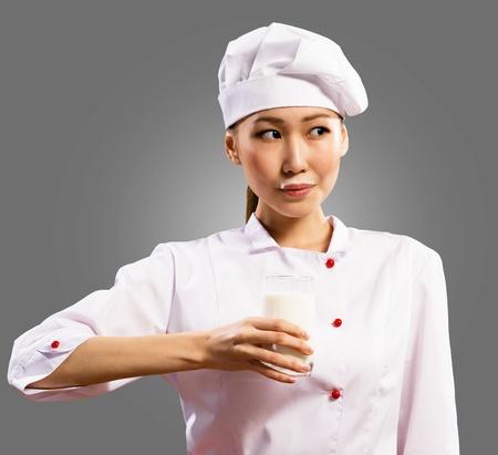 milk mustache: female asian chef holding a glass of milk, a milk mustache