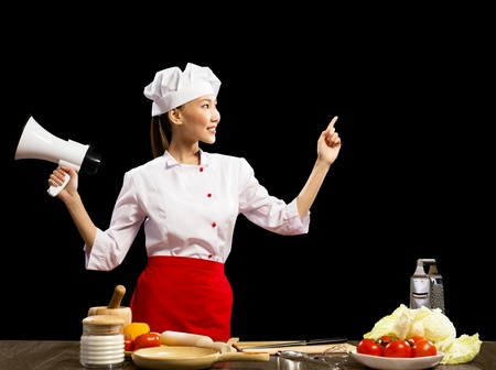 Asian female chef holding a megaphone and points a finger at a place for text photo