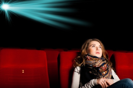 young attractive woman sitting in a cinema, enjoying a movie Stock Photo - 17136933