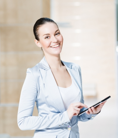 android tablet: Portrait of a business woman in the tablet at the office, turned around and looking at the camera Stock Photo