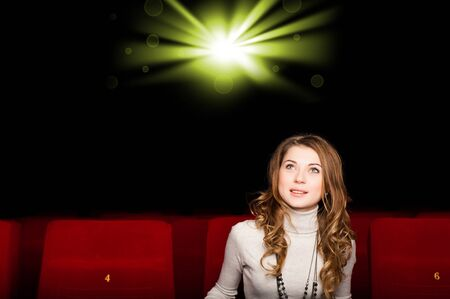 young attractive woman sitting in a cinema, enjoying a movie photo