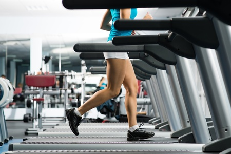 health care facility: woman running on a treadmill in a fitness club, sport in the fitness club Stock Photo