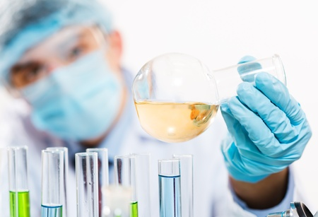 scientist working in the lab, in protective mask and cap, examines a test tube with liquid Stock Photo - 17136940