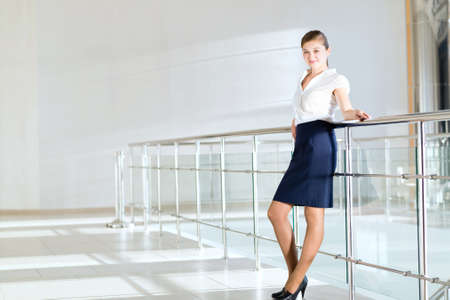 obscured face: Business woman standing in the lobby of the office, based on the railing of the balcony Stock Photo