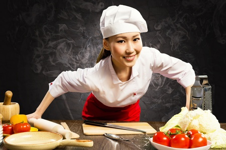 Asian woman cook leaned over the table and looking into the camera photo