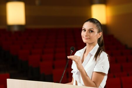 Portrait of a business woman holding a microphone and looks ahead Stock Photo - 17155341