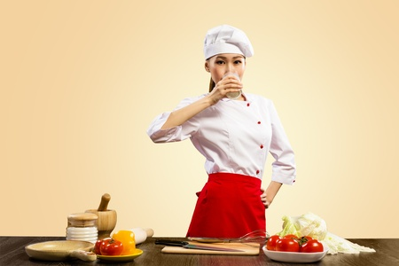 Asian female cook drinking milk and looks ahead Stock Photo - 17221836