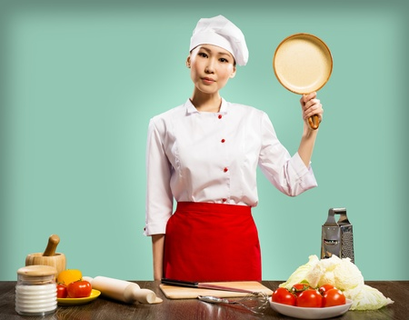 Chinese woman chef holding a ceramic pan, quietly looking at the camera photo