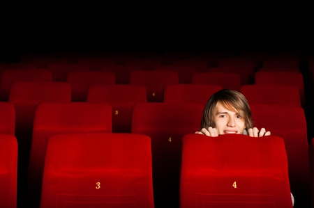 young man in the cinema hiding behind a chair, watching scary movie Stock Photo - 17237898