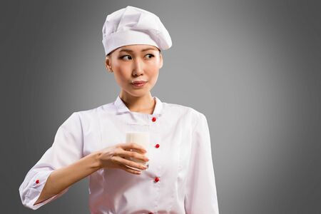 Asian woman chef drinking milk, milk mustache on her lips photo