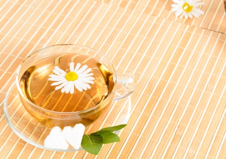 A teacup with herbal chamomile tea and flower photo