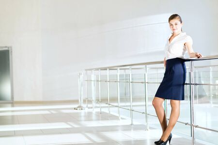 Business woman standing in the lobby of the office, based on the railing of the balcony photo