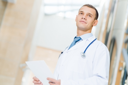 hospital background: Portrait of a doctor holding papers in hand, office space Stock Photo