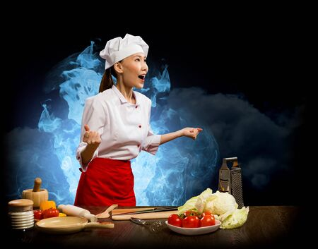 Asian woman furious chef shouting with clenched fists, smoke and blue flames of rage photo