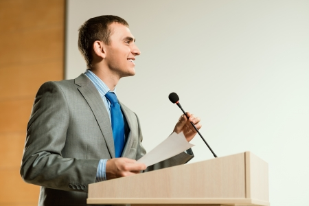 podium: male speaker looks into the room and said into the microphone, speech at the conference