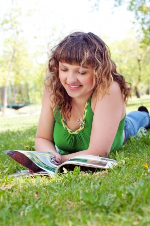 portrait of a young woman in a park reading a magazine photo