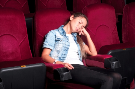 Woman asleep in a movie theater when watching a boring movie photo