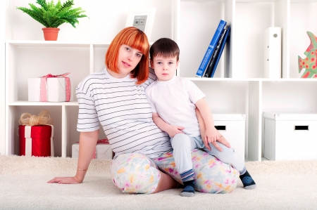 portrait of a pregnant woman and her son, at home photo