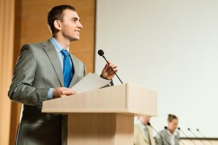 locuteur masculin regarde dans la pièce et dit dans le micro, la parole lors de la conférence