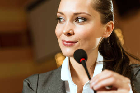 Portrait of a business woman holding a microphone and looks ahead Stock Photo - 17362226