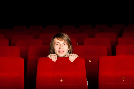 young man in the cinema hiding behind a chair and smiling Stock Photo - 17362212