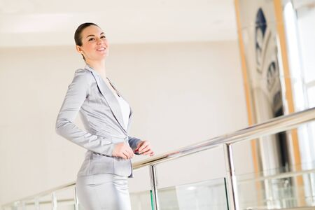obscured face: Portrait of a successful business woman standing near railing Stock Photo