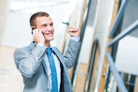 successful businessman talking on the phone and is happy to receive breaking news, to be successful in business photo