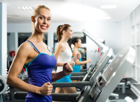 young women running on a treadmill, exercise at the fitness club photo