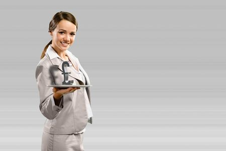 attractive business woman holding a tablet with british pound, place for text photo
