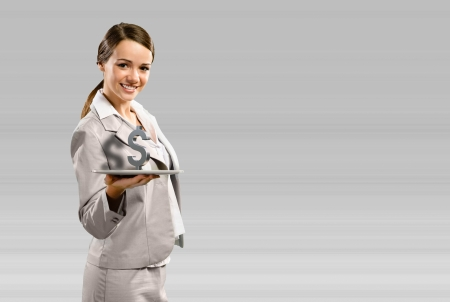 attractive business woman smiling and holding a tablet, with a dollar sign, concept of business success Stock Photo - 17425094