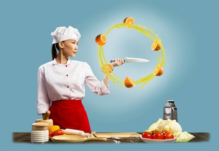 Asian female chef holding a knife, around which revolve sliced ​​oranges photo