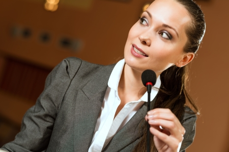 Portrait of a business woman holding a microphone and looks ahead Stock Photo - 17478032