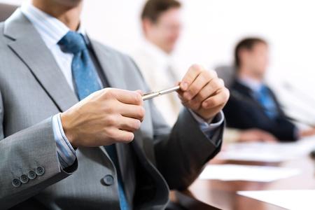 sala de reuniones: hombre de negocios sentado en una mesa y sosteniendo una pluma Foto de archivo