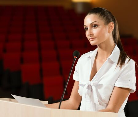 Portrait of a business woman holding a microphone and looks ahead photo