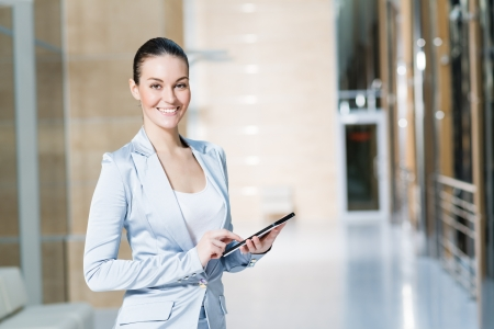 Portrait of a business woman in the tablet at the office, turned around and looking at the camera Stock Photo