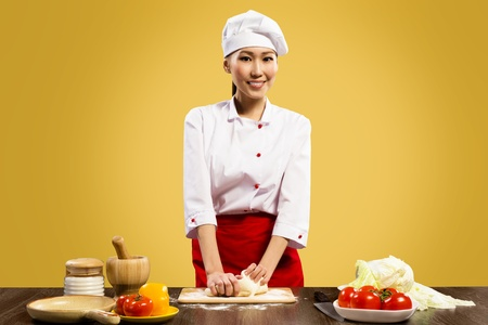 Asian female chef cooking pizza dough, looks at the camera and smiling photo