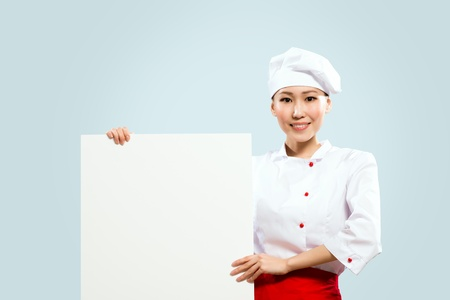 Asian female chef holding a white poster for the text photo