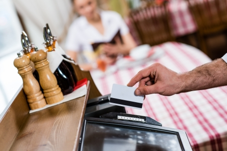 inserts: waiter inserts the card into a computer terminal, against visiting the restaurant